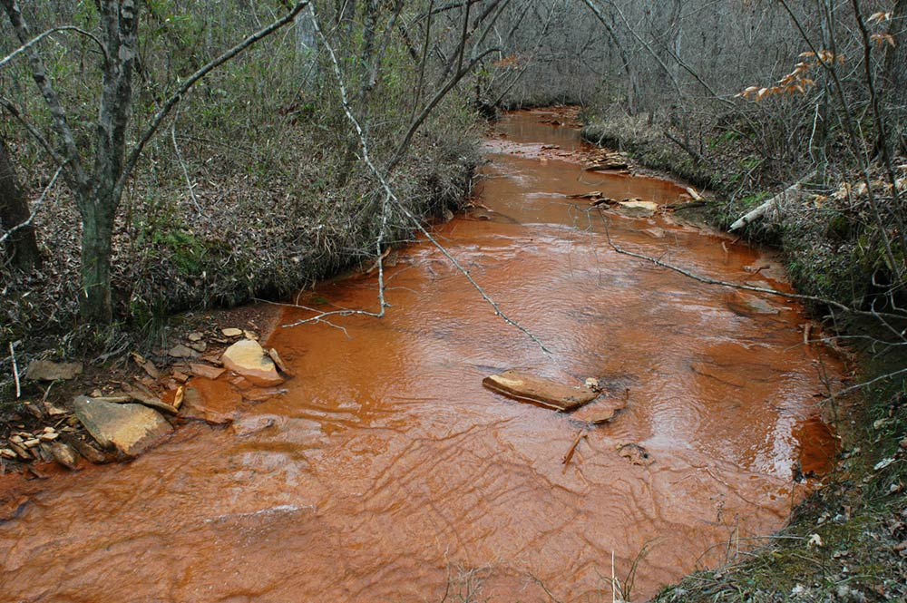 burnt cane creek stained orange from acid mine drainage