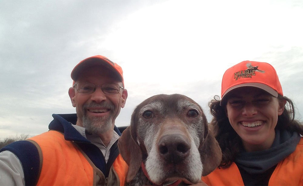 male and female hunters in orange taking a selfie with hunting dog