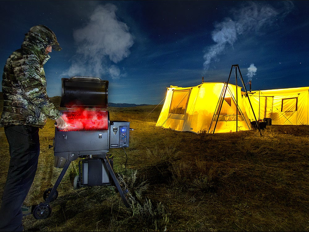 hunter cooking on a stove while wal tent hunting