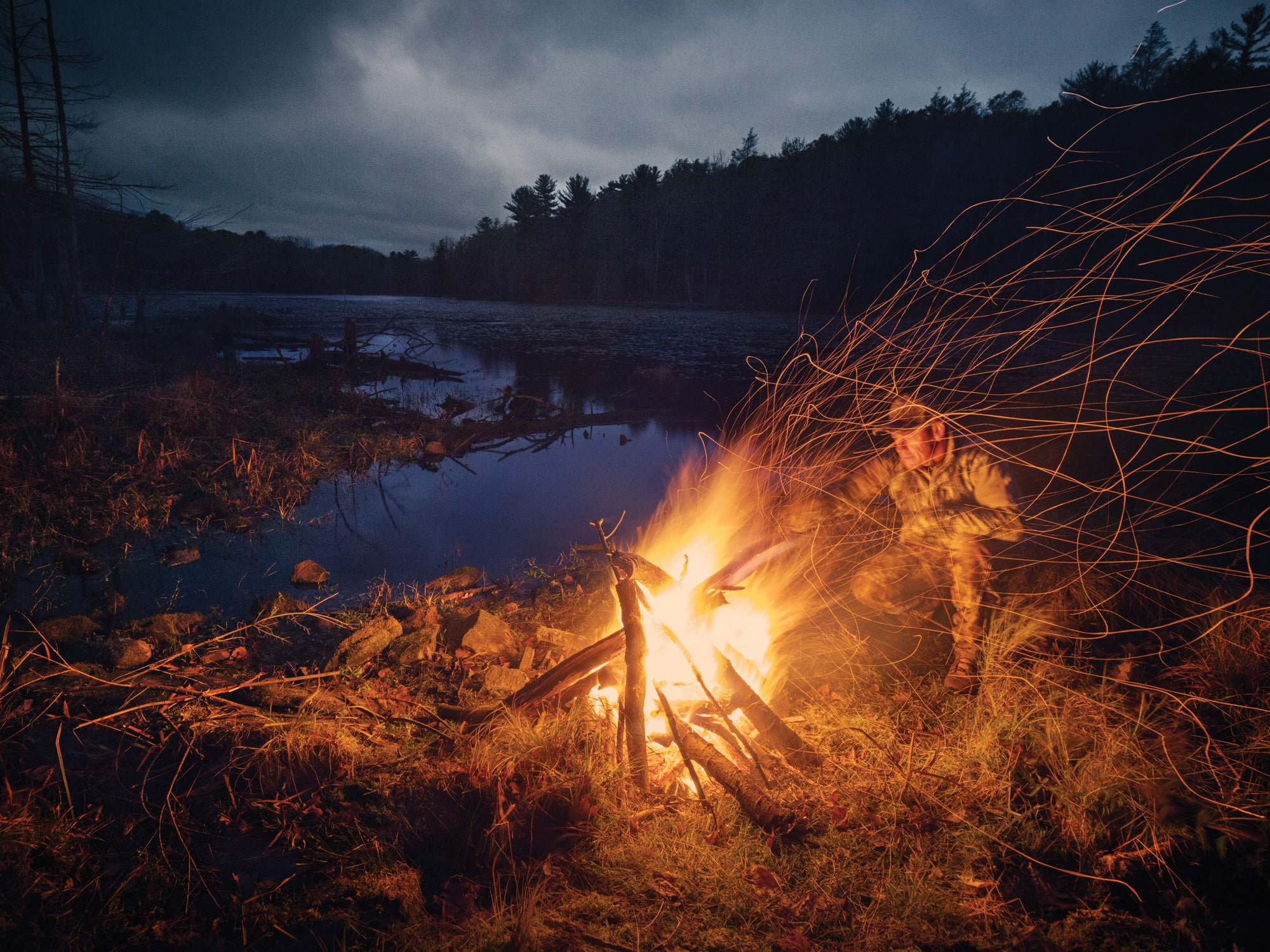 A man building a fire in the wilderness.