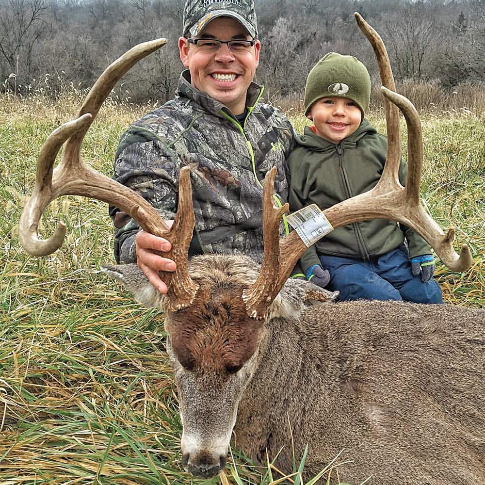 Jared Lurk with son and trophy buck