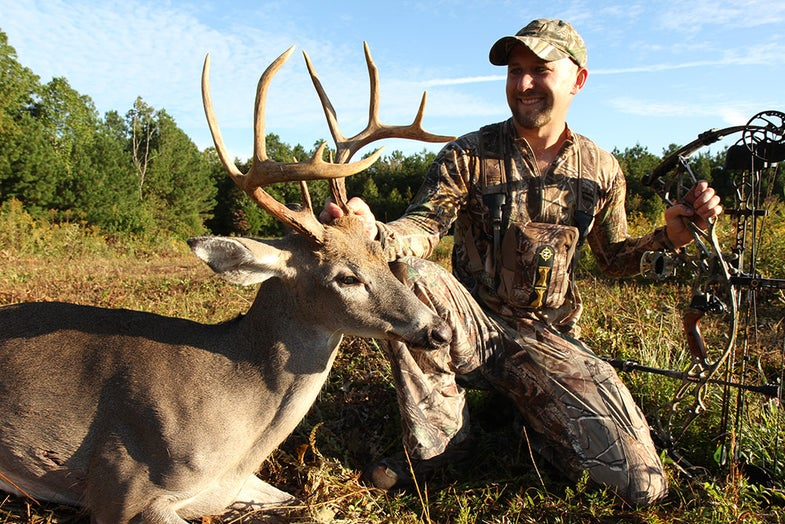 will brantley kneeling next to a 10-point buck
