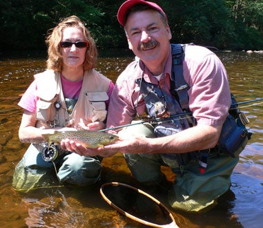 man and woman holding a trout
