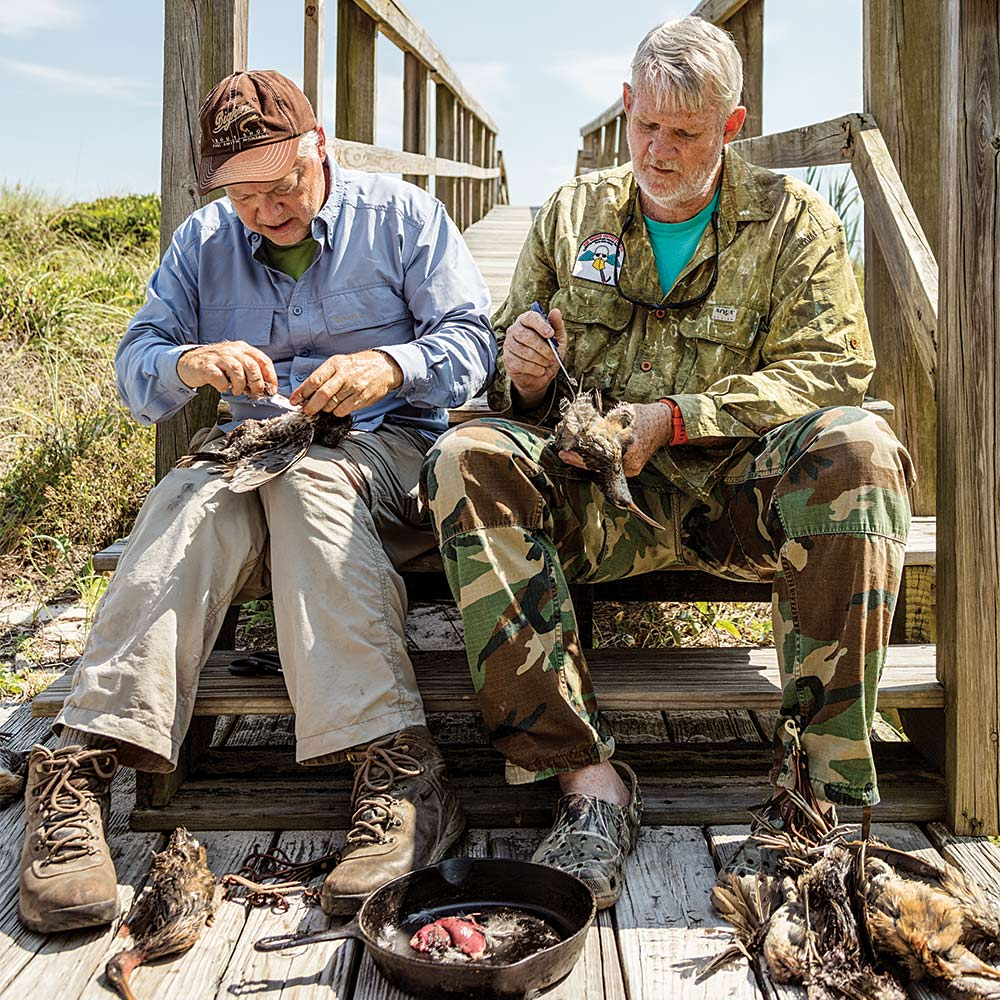 two hunters cleaning rail birds for cooking
