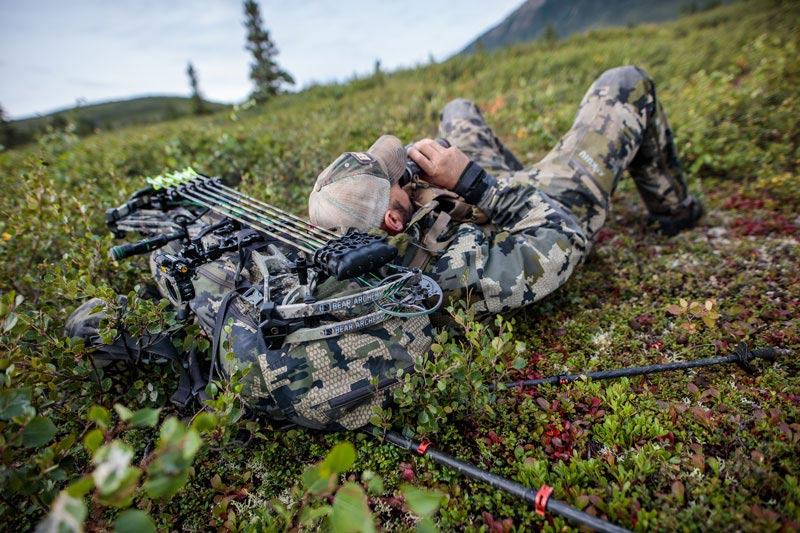 bowhunter lying on great with binoculars