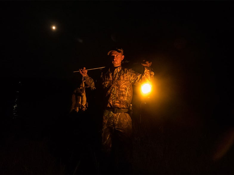 hunter holding squirrels at night