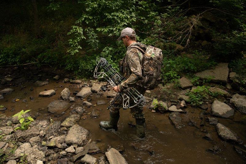 bowhunter walking through stream