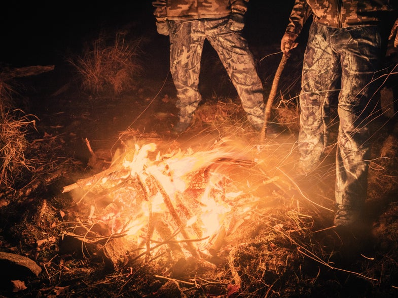 Two Hunters tend the perfect campfire at night.