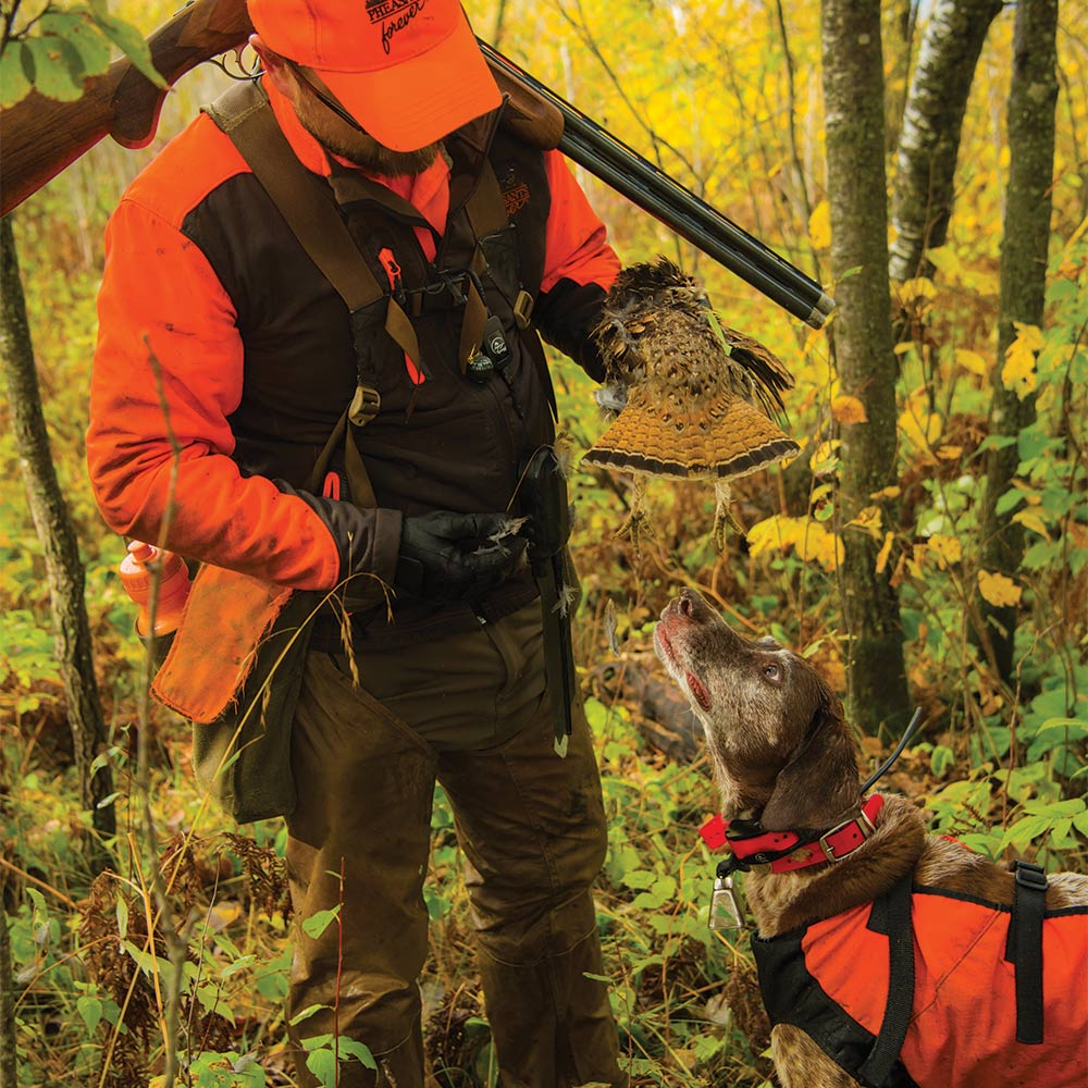 man holding grouse over hunting dog