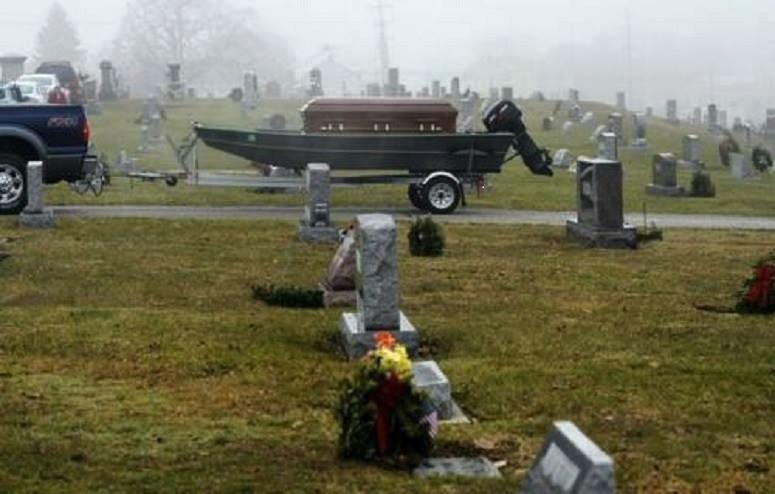 Casket in fishing boat in cemetery