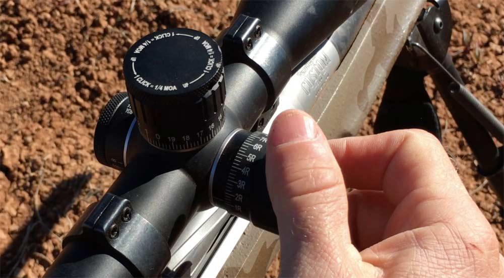 shooter making wind adjustments on rifle