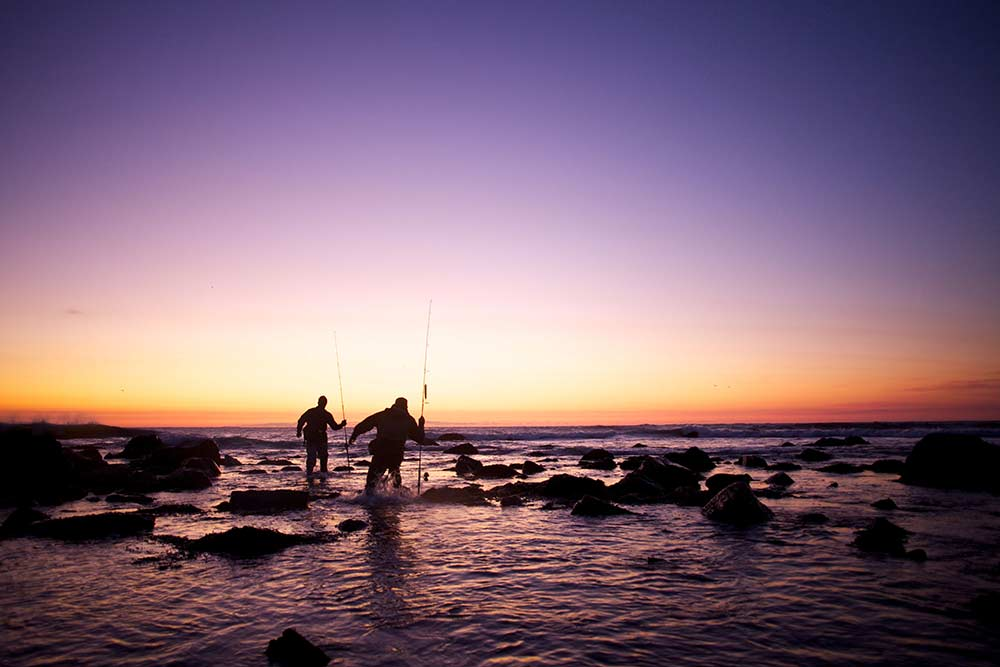 two anglers fishing shoreline at sunset