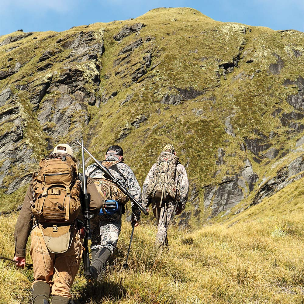 Hunters hiking up a New Zealand hill side