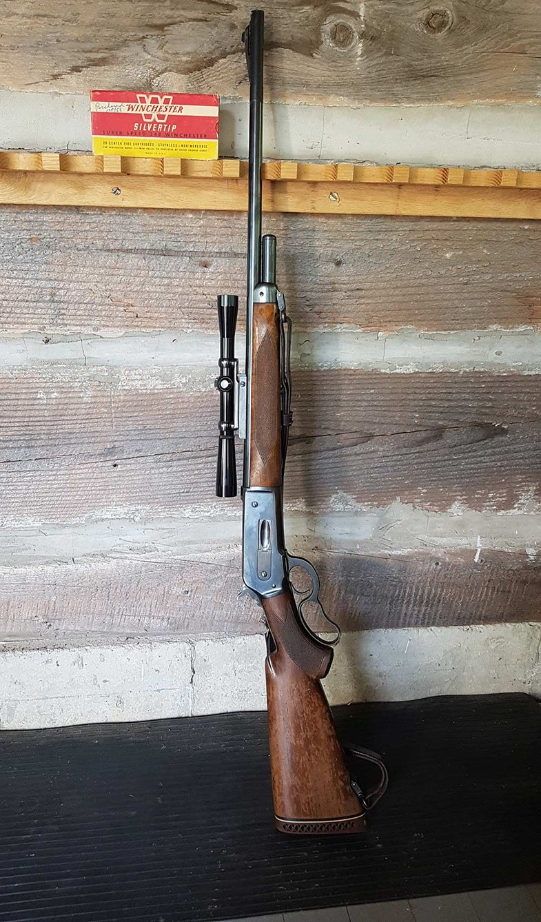a vintage winchester model 71 leaning against the wall