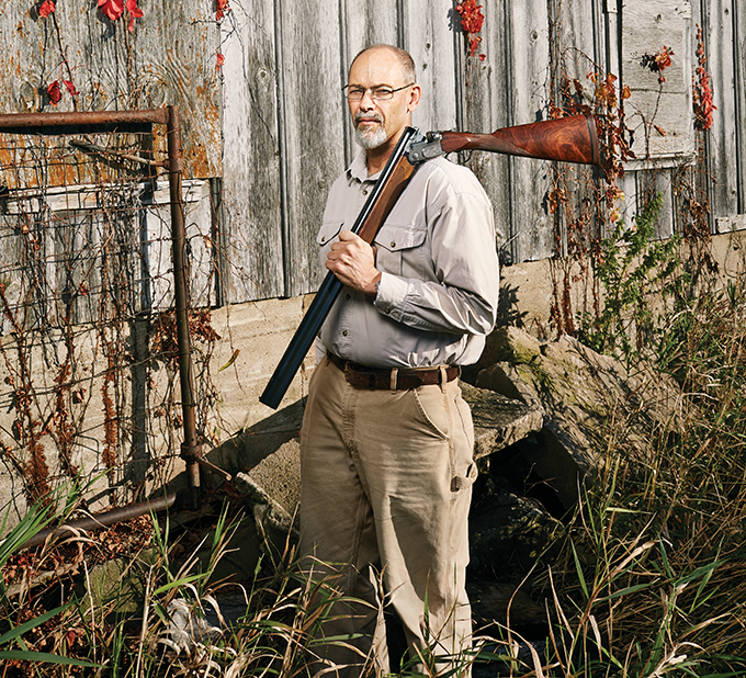 A man holds a shotgun over his shoulder.