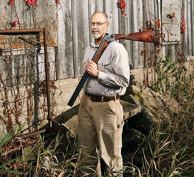 A man holds a shotgun over his shoulder.