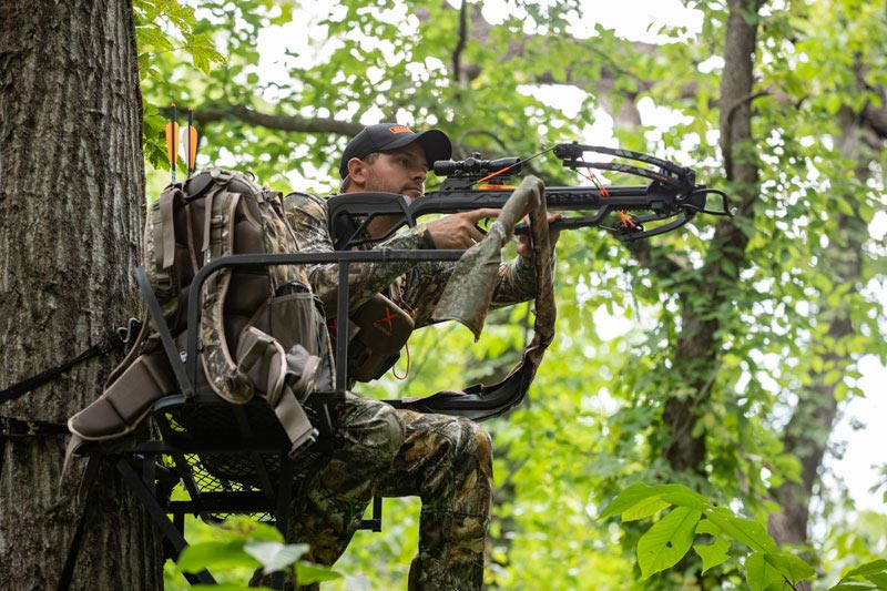 bowhunter aiming crossbow in a treestand