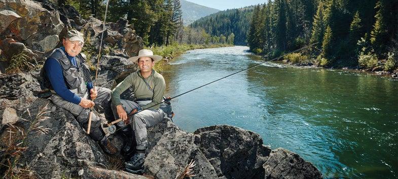 yvon chouinard and kenton carruth sitting on rocks by stream