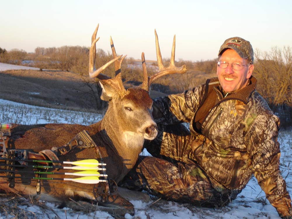 Bowhunter with an Iowa buck