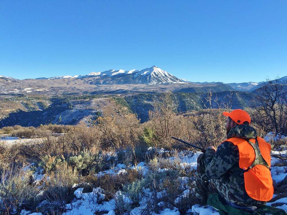 hunter sitting on a hillside in gunnison national forest