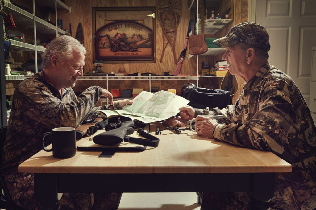Two hunters planning their hunts while looking at a map.