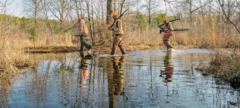 three hunters walking through swamp