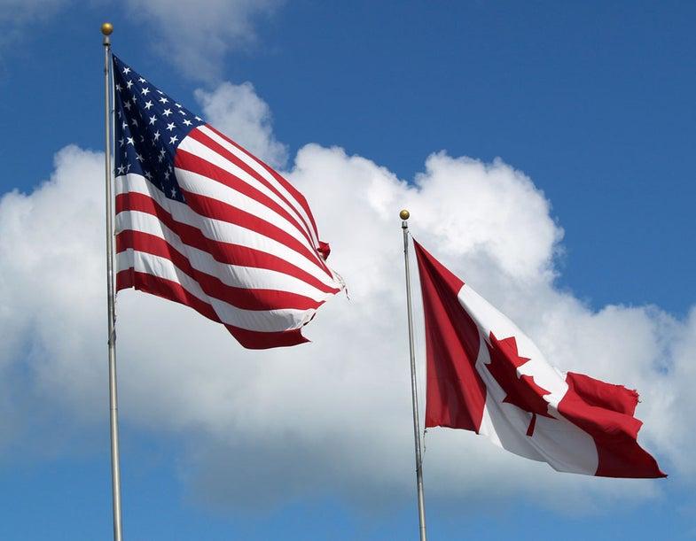 american flag, canadian flag, blue sky