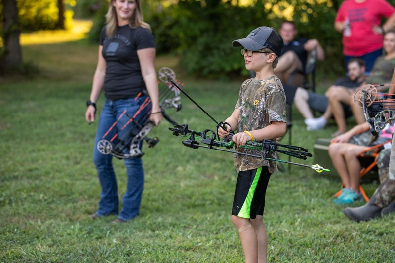 young boy holding a bow