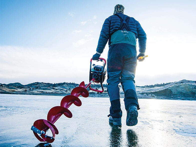 man carrying ice drill