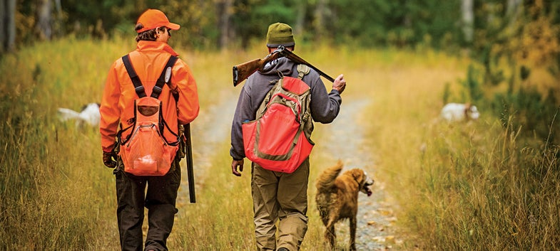 two men and a hunting dog hunting grouse