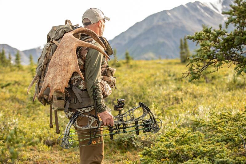 bow hunter with moose antlers on his backpack