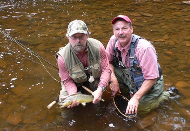 two fishermen holding a trout