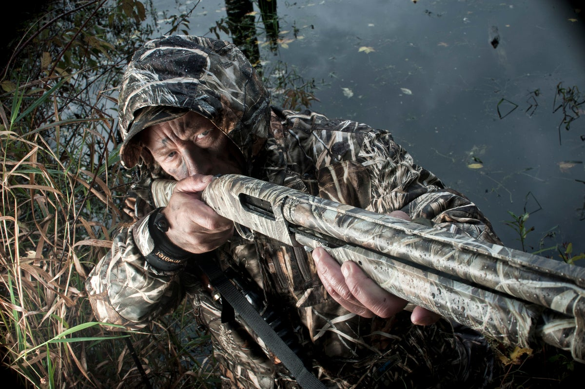 A hunter aiming a shotgun in the weeds.