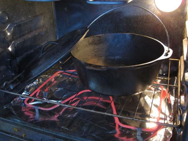 Rinse the cast iron dutch oven and dry it off in the oven.