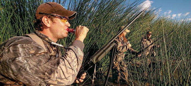 teal hunters calling in marsh