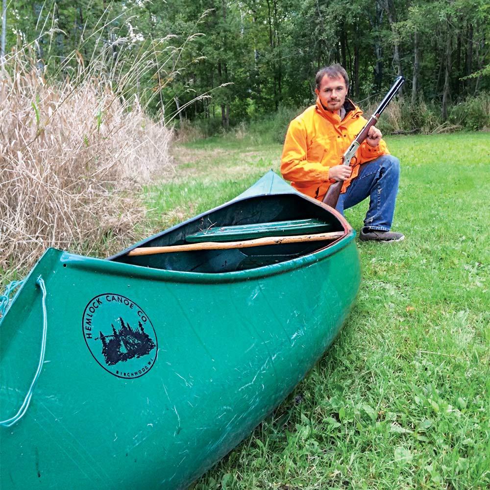 Hunter with a gun kneeling by canoe