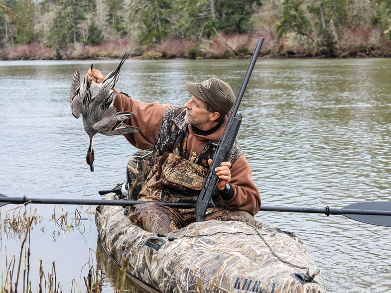 hunter in kayak holding a duck