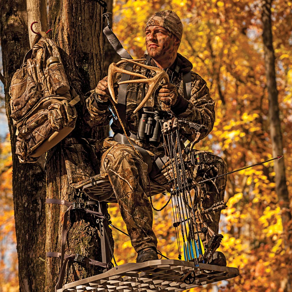 A hunter in tree stand rattling antlers