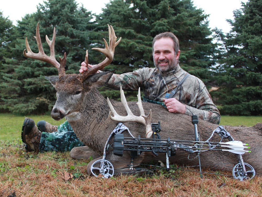 Bow hunter with a trophy buck