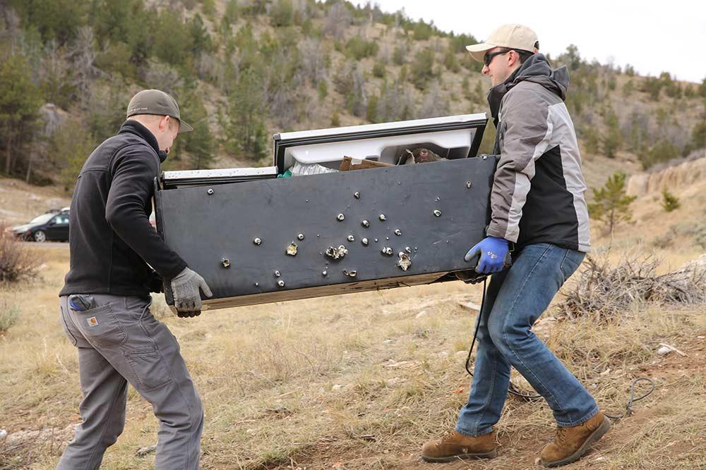 two men carry fridge