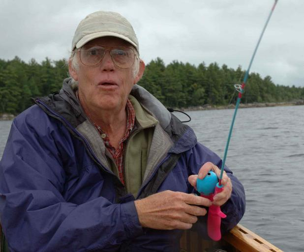 A man in fishing gear holds up a kids fishing pole.