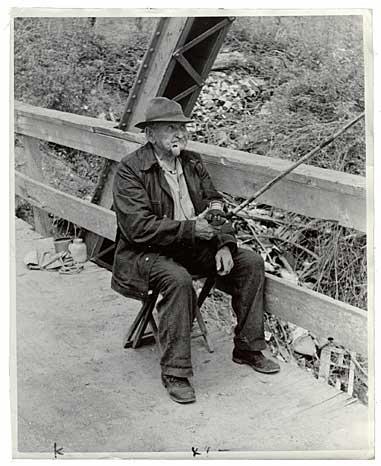 old fisherman on bridge