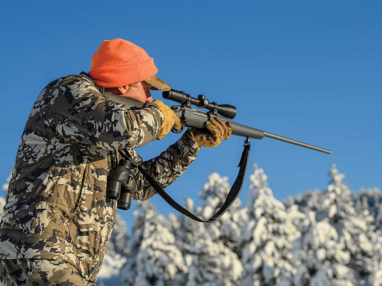 hunter aiming rifle in snowy woods