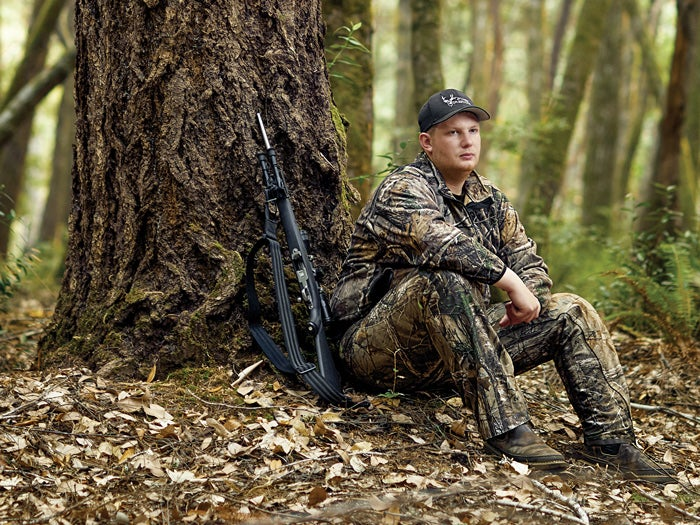 A young hunter in full camo gear sits by a tree in the woods.