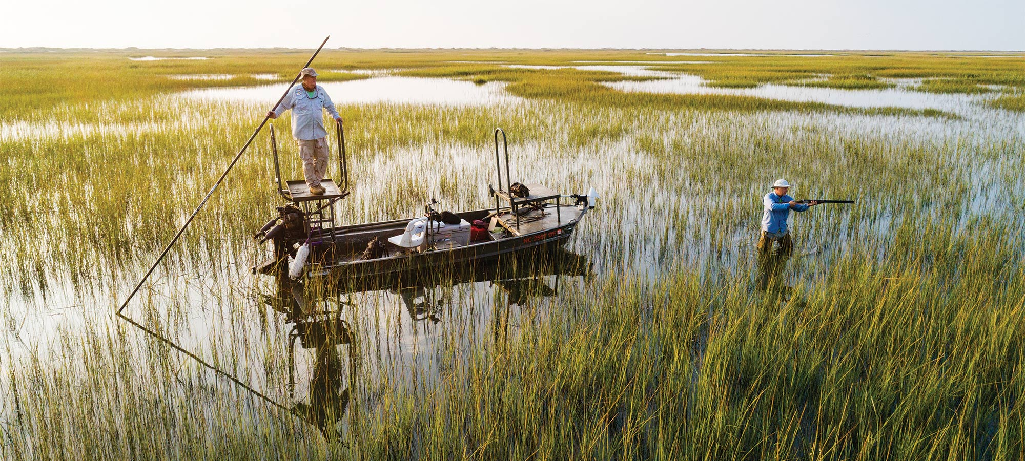 two hunters in a marsh with a john boat