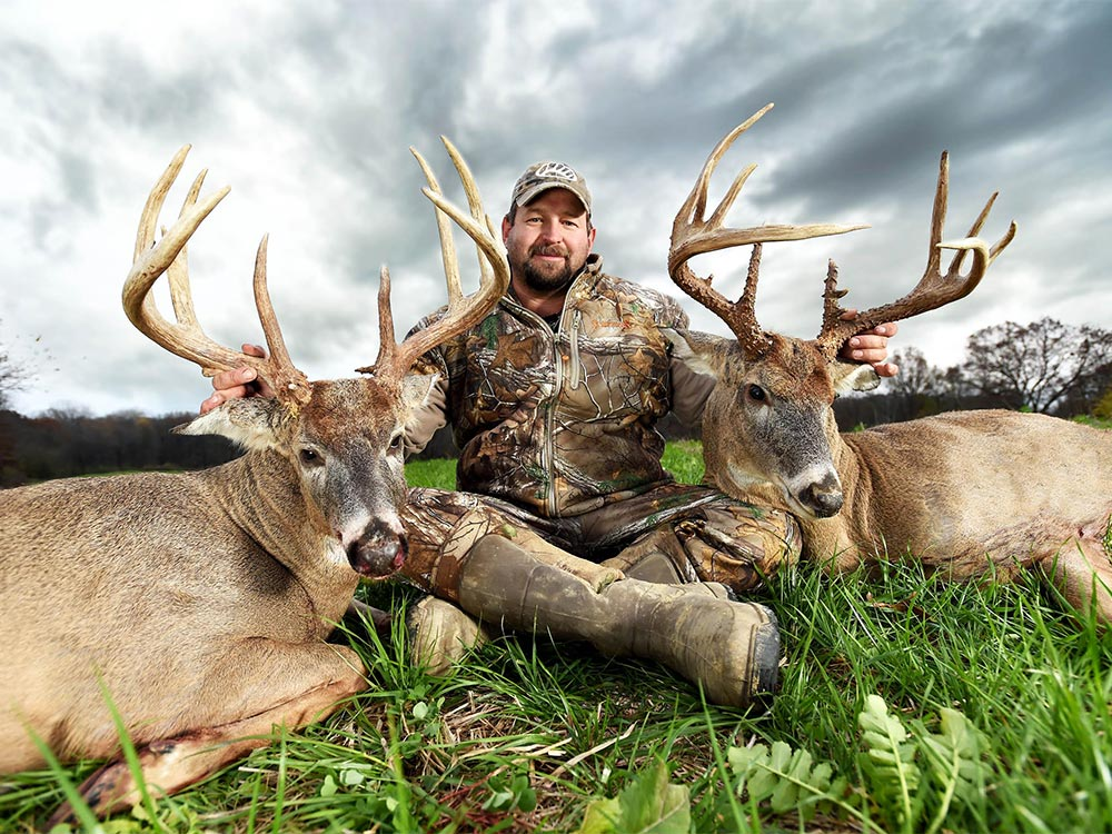 Hunter with a duo of trophy bucks
