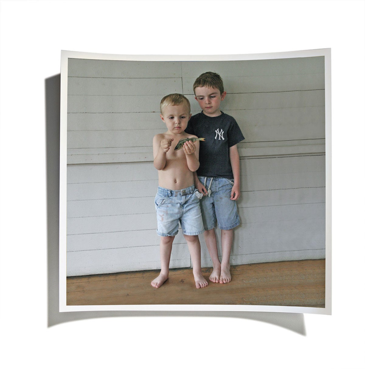 Two young boys holding a fish on a front porch.