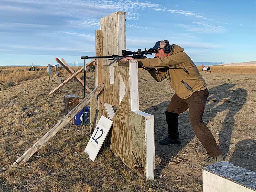 man aiming rifle on shooting barricade