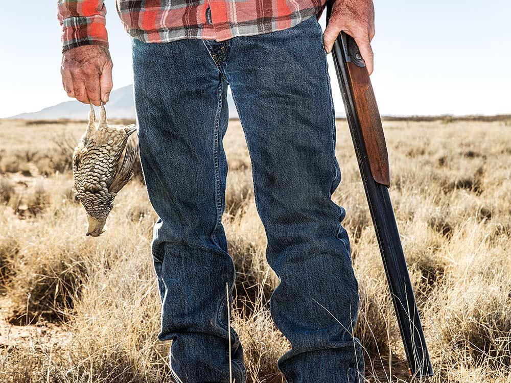 hunter holding shotgun and quail
