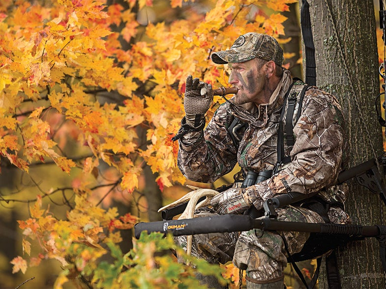 Hunter calling buck from tree stand